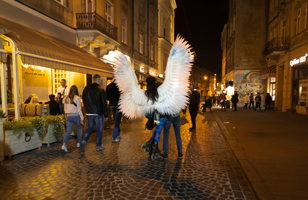 Lviv, Ukraine - Oct 13, 2018: Young girl with angel wings and roller skates on the streets of Lviv at night
