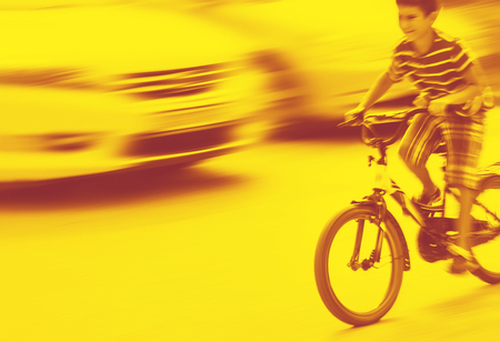 Duotone yellow and red image of dangerous city traffic situation with a boy on bicycle and cars in motion blur