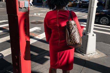 NEW YORK, USA - Sep 23, 2017: Manhattan street scene. A woman in a red dress is standing near emergency button - outdoor system police and fire call. Editorial