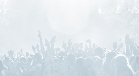 Crowd of spectators at a concert in light blue tonality. High key background with a people on an open playground at a concert. Abstract soft focus image with copy space 免版税图像