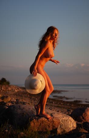 Giovane donna con un cappello bianco in piedi su una pietra in riva al mare sotto i raggi del sole al tramonto