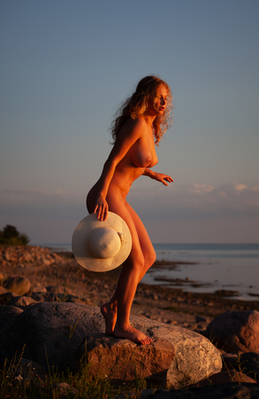Young nude woman with a white hat standing on a stone by the sea in the rays of the sunset sun