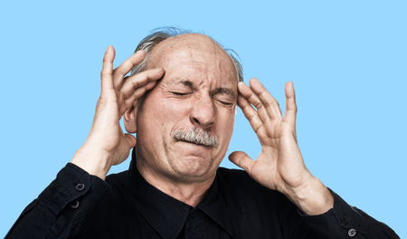 Old man feeling tired and headache. Strong headache. Health care concept. Old man suffering from a headache isolated on blue background