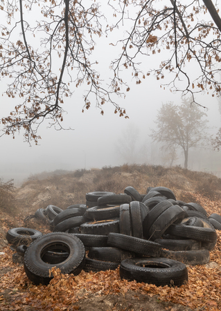 Ecological concept. Heap of old tires. Dump of old used tires in the city on a foggy autumn day