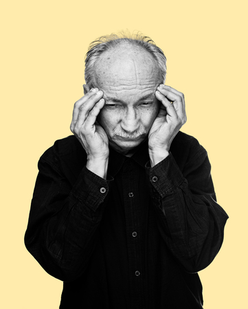 Health care concept. Black and white image of an old man suffering from a headache isolated on yellow background