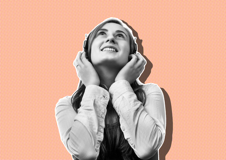 Lifestyle concept. Young happy woman listening to music on headphones.  Magazine style collage with copy space and trendy living coral color background