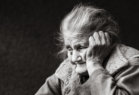 Old age and lifestyle concept. Black and white portrait of a very old and tired wrinkled woman outdoors. Very old hoary woman face closeup portrait. Aging process - very old senior women Reklamní fotografie