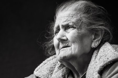 Old age and lifestyle concept. Black and white portrait of a very old and tired wrinkled woman outdoors. Very old hoary woman face closeup portrait. Aging process - very old senior women Stok Fotoğraf