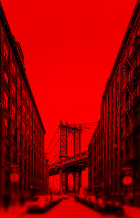 Manhattan Bridge and Empire State Building seen from Brooklyn, New York. Image in dramatic red tonality with a blurred foreground.
