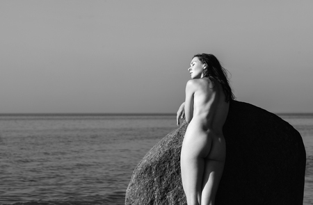 Naked girl outdoors enjoying nature. Beautiful young woman stands among the big stones against the sea. Lady with perfect body on the nudist beach. Black and white image