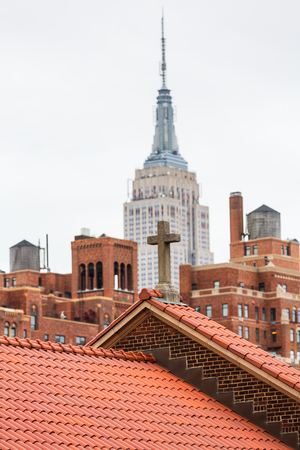 NEW YORK, USA - Apr 29, 2016: New York City skyline and roofs of Manhattan. Stone cross on the roof of a church in Manhattan with Empire State Building. Midtown Manhattan from High Line Park