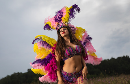 Young woman in bright colorful carnival costume posing outdoors.