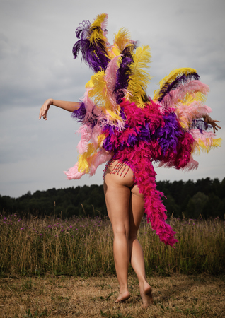 Young naked woman in bright colorful carnival costume posing outdoors. Beautiful half naked young girl. Semi naked female dancer