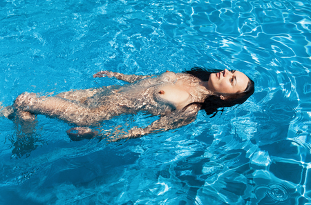 Concepto de belleza y estilo de vida saludable. Hermosa mujer joven en piscina. Mujer joven disfruta nadando en la piscina