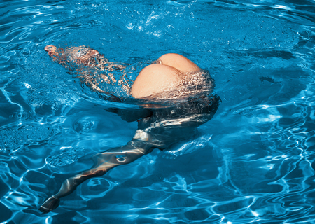 Beauty and healthy lifestyle concept. Beautiful young nude woman in swimming pool. Young naked woman enjoy swimming in the pool Stockfoto