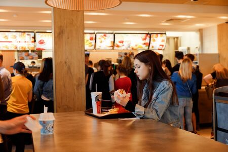 KYIV, UKRAINE - May 05, 2017: Young people have a rest and eating in a Mcdonalds in Kyiv, Ukraine. Mcdonalds is a very good place for young people.  Illustrative editorial.