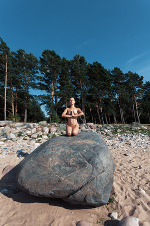 Stile di vita sano e concetto di bellezza. Ragazza nuda all'aperto. Yoga nudo. Bella donna seduta in una posa yoga all'aperto Archivio Fotografico