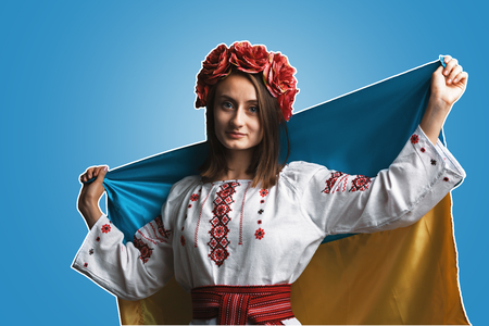Ukraine patriotic concept. Beautiful girl in the Ukrainian national suit with Ukrainian flag. Magazine style collage with copyspace