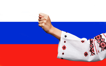 Political metaphor. Russian Ukrainian conflict. Female hand in the Ukrainian national costume showing the fig against the background of the Russian flag