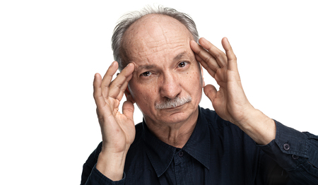 Health and illness concept. Elderly man suffers from headache and holds his head by hand isolated on white with copy space