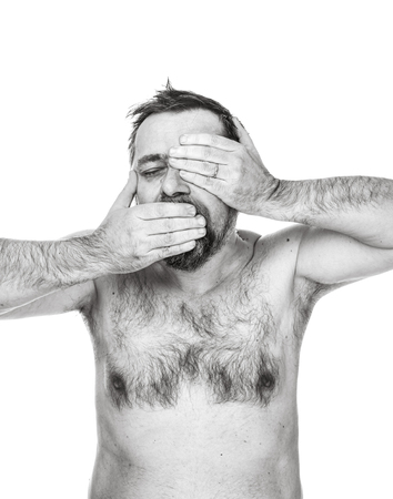 Brutal bearded man with bare-chested posing over white wall. Portrait of a man with a torso. A man gesticulates and holds his hands on his head.