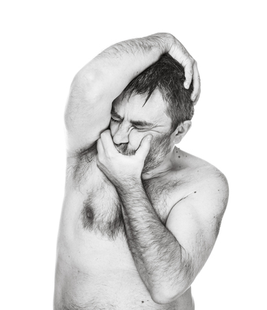 Brutal bearded man with bare-chested posing over white wall. Portrait of a man with a naked torso. Man holding his head with his hands