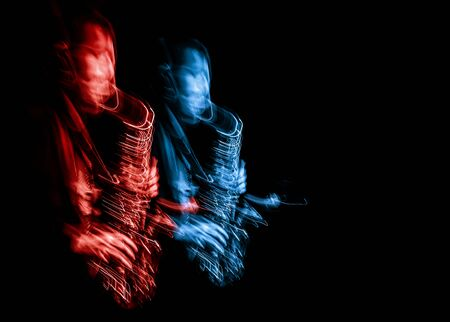 Jazz music concept. Abstract motion blurred image of saxophone player performing on stage. Sax player going crazy. Stock Photo