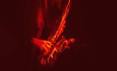 Jazz music concept. Abstract motion blurred image of saxophone player performing on stage. Sax player going crazy.