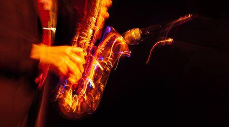 Concept de musique jazz. Image floue de mouvement abstrait du saxophoniste jouant sur scène. Le saxophoniste devient fou.
