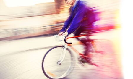 Abstract blurred image of cyclist on the city roadway. Intentional motion blur. Vintage filter with intentional color shift