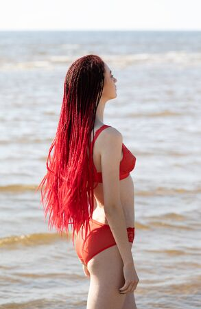 Beautiful girl outdoors enjoying nature. Seminude girl with scarlet dreadlocks in a red bathing suit sunbathes on the beach Foto de archivo