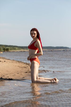 Beautiful girl outdoors enjoying nature. Seminude girl with scarlet dreadlocks in a red bathing suit sunbathes on the beach Stock Photo