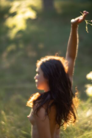 Soft focus blurred image of a young nude woman in sun light on the forest background. Image in a soft romantic and vintage style Фото со стока