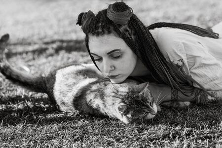 Black and white image of an young woman with dreadlocks in national dress lying on the grass and playing with the cat. Outdoors portrait