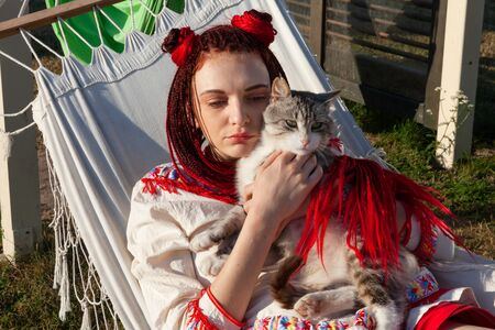 Young woman with scarlet dreadlocks in national dress lying in a hammock and playing with a cat. Outdoors portrait
