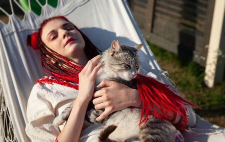 Young woman with scarlet dreadlocks in national dress lying in a hammock and playing with a cat. Outdoors portrait. Focus on cat Stock fotó