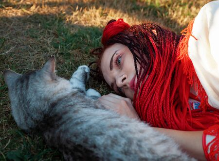 Young woman with scarlet dreadlocks in national dress lying on the grass and playing with the cat. Outdoors portrait Stock fotó