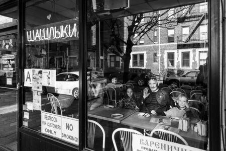 NEW YORK, USA - Apr 27, 2016:  Russian Barbecue Cafe on Brighton Beach in New York. Elderly man with grandchildren order breakfast