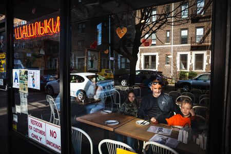 NEW YORK, USA - Apr 27, 2016: Barbecue Cafe on Brighton Beach in New York. Elderly man with grandchildren order breakfast. The inscription on the Russian - kebabs