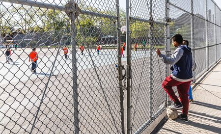 NEW YORK, USA - Apr 28, 2016: Boys watch the children play football in the childrens playground in Brooklyn, New York City