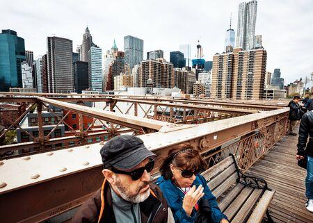 NEW YORK, USA - Apr 29, 2016: NYC street scene. New Yorkers and tourists walking on the Brooklyn Bridge. Manhattan skyline in background