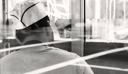 NEW YORK, USA - Apr 28, 2016: Manhattan street scene. Portrait of a seller at a fast food kiosk in Manhattan. The face is reflected in the mirror. Black and white image