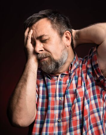 Sick middle aged man. Healthcare, pain, stress and age concept. Senior man suffering from headache. Elderly man has a headache. Human emotions, facial expressions, life perception, aging, depression