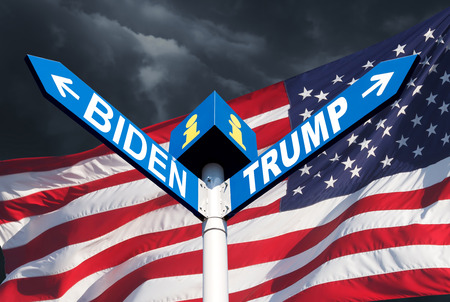 Confrontation between Biden and Trump. The names of Presidents Donald Trump and Joe Biden on the roadside sign on the background of the American flag and a stormy sky Publikacyjne
