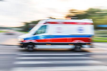Ambulancia en llamada de emergencia en movimiento borroso. Ambulancia en la ciudad sobre un fondo borroso