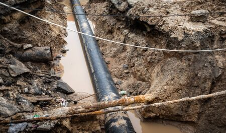 Repair of roads and underground utilities. Big trench on the road with a pipe, the process of repair or replacing of water pipes in big city. �¡onstruction and repair of underground water