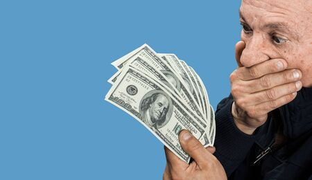 Lucky old man holding dollar bills on a blue background with copy space