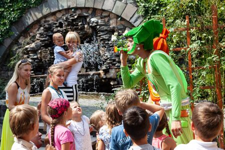 UZHGOROD, UKRAINE - Aug. 20, 2015: Clowns show soap bubbles to children during a children's holiday. Children and adults play soap bubbl Editorial