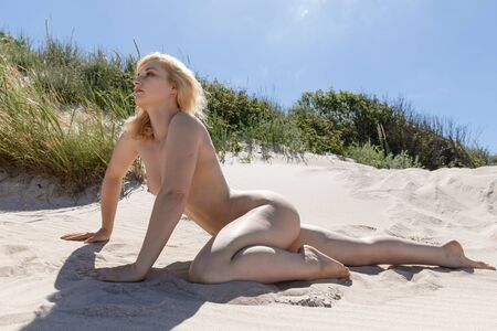 Lifestyle and beauty concept. Beautiful nude girl enjoying nature. Young naked blonde woman among the sand dunes on a sandy beach. Nude woman posing on sea beach.