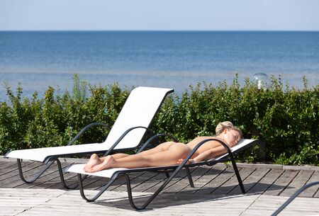 Beauty and healthy lifestyle concept. Naked woman with dreadlocks sunbathing on sunbed near the pool. Archivio Fotografico